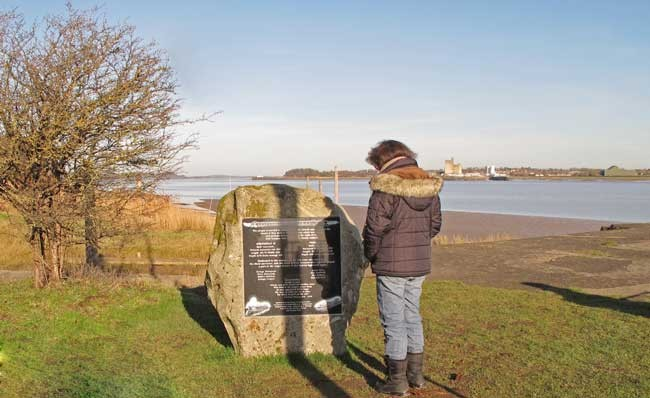 A visitor inspecting the Severn Rail Bridge memorial at Lydney Harbour.